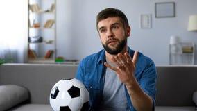 Jeune homme observant nerveusement le match de football sur la maison de TV, frustrée à la perte d'équipe image stock