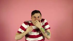 Jeune homme occasionnel beau couvrant des yeux de mains et faisant le geste d'arrêt avec l'expression triste et de crainte Gêné e banque de vidéos