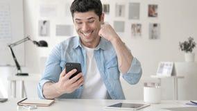 Jeune homme occasionnel célébrant le succès sur Smartphone banque de vidéos