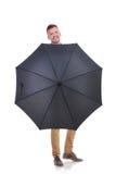 Jeune homme occasionnel derrière un parapluie noir Images stock