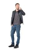 Jeune homme occasionnel parlant au téléphone portable riant et regardant l'appareil-photo Image stock