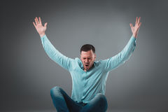 Jeune homme occasionnel s'asseyant sur le plancher avec ses jambes croisées et encourageant avec ses mains dans le ciel tout en c Photographie stock