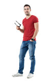 Jeune homme occasionnel satisfaisant heureux tenant des lunettes de soleil souriant à l'appareil-photo Photo stock