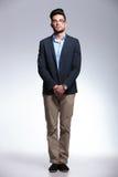 Jeune homme occasionnel se tenant sur le fond gris Photo stock