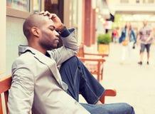 Jeune homme occasionnel triste soumis à une contrainte d'affaires s'asseyant en dehors de l'entreprise photographie stock