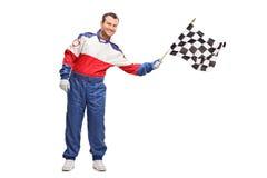 Jeune homme ondulant un drapeau à carreaux de course Photographie stock libre de droits