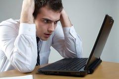 Jeune homme ou étudiant perplexe d'affaires avec l'ordinateur portatif à la table Photo libre de droits