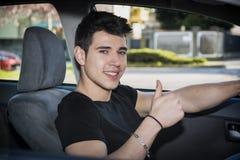 Jeune homme ou adolescent heureux faisant le pouce conduisant  Photo stock