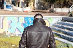 Jeune homme par derrière avec la veste en cuir dans un espace abandonné photographie stock libre de droits