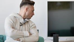 Jeune homme parlant à l'assistant électronique futé de maison de haut-parleur clips vidéos