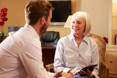 Jeune homme parlant au conseiller employant Digital Tabl image stock