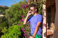 Jeune homme parlant au téléphone au balcon Photographie stock