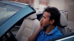 Jeune homme parlant au téléphone intelligent se reposant sur la voiture de cabriolet de siège conducteur au stationnement banque de vidéos