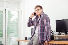 Jeune homme parlant au téléphone portable dans le bureau photo libre de droits