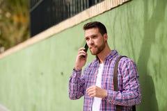 Jeune homme parlant avec son téléphone intelligent à l'arrière-plan urbain durée Photos libres de droits