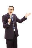 Jeune homme parlant dans un microphone et faire des gestes Images stock