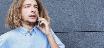 Jeune homme parlant sur l'espace extérieur de copie de téléphone Images libres de droits