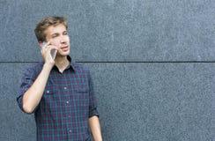 Jeune homme parlant sur l'espace extérieur de copie de téléphone Photos stock