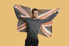 Jeune homme patriote soulevant le drapeau britannique au-dessus du fond coloré Photographie stock