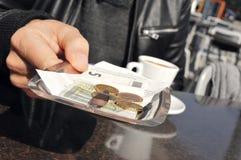 Jeune homme payant la facture dans la terrasse d'un café Photos stock