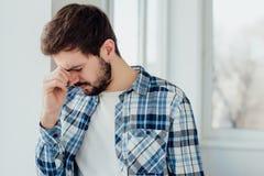 Jeune homme pensant à la fenêtre photographie stock libre de droits