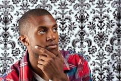 Jeune homme pensant avec une main en fonction Photos libres de droits