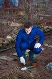 Jeune homme plantant l'ail photos stock