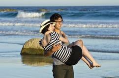 Jeune homme portant le joli femme au bord de la mer Photos stock