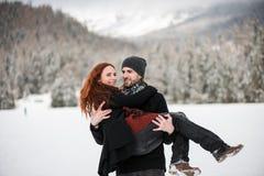 Jeune homme portant son amie dans des bras Photographie stock
