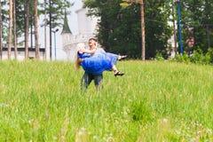 Jeune homme portant son amie dans des ses bras sur le champ d'herbe Couplez avoir l'amusement en nature un jour d'été Images stock