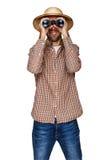 Jeune homme portant un casque de moelle regardant par des jumelles avec une expression étonnée photographie stock