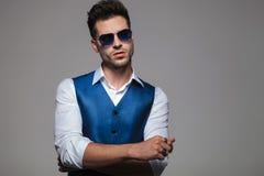 Jeune homme portant un gilet bleu se tenant avec des mains pliées Photos stock
