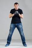 Jeune homme posant dans le studio avec les gants fonctionnants Image libre de droits