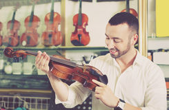 Jeune homme positif achetant les violons traditionnels dans le magasin Photo stock