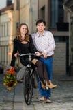 Jeune homme poussant son amie sur la bicyclette Photographie stock