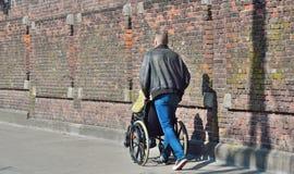 Jeune homme poussant une personne plus âgée dans son fauteuil roulant Photographie stock libre de droits