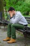 Jeune homme préoccupé s'asseyant en parc Image stock