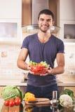 Jeune homme préparant la nourriture à la maison Photographie stock