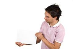 Jeune homme présent une page blanc Photographie stock