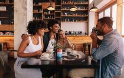 Jeune homme prenant des photos de ses amis dans un café Photographie stock libre de droits