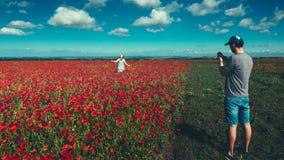 Jeune homme prenant des photos sur le smartphone, jeune fille courant à travers le champ des pavots rouges, concept de tourisme d Photographie stock