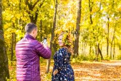 Jeune homme prenant la photo de son amie avec le téléphone portable en nature d'automne Images libres de droits