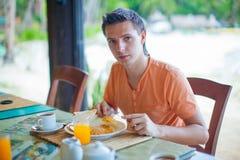 Jeune homme prenant le petit déjeuner au restaurant de station de vacances Photographie stock libre de droits