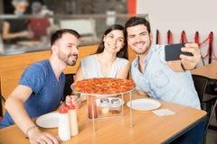 Jeune homme prenant le selfie avec des amis ayant la pizza Photographie stock libre de droits
