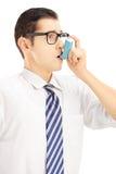 Jeune homme prenant le traitement d'asthme Images stock