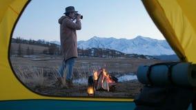 Jeune homme prenant une photo avec DSLR dans le matin calme d'été après nuit dans la tente rouge 20s 4k banque de vidéos
