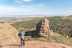 Jeune homme prenant une photo d'un Rodeno Boulder dans Perecens, Teruel, Espagne photo libre de droits