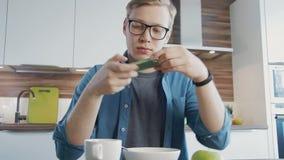 Jeune homme prenant une photo de son petit déjeuner banque de vidéos