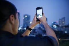 Jeune homme prenant une photo du paysage urbain du haut du bâtiment image libre de droits