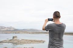 Jeune homme prenant une photo en Sardaigne, Italie Images libres de droits